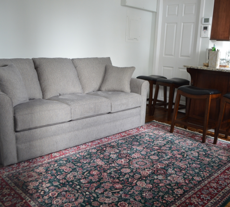 Photograph of living room area with grey couch, a multicolored rug, and 3 stools.