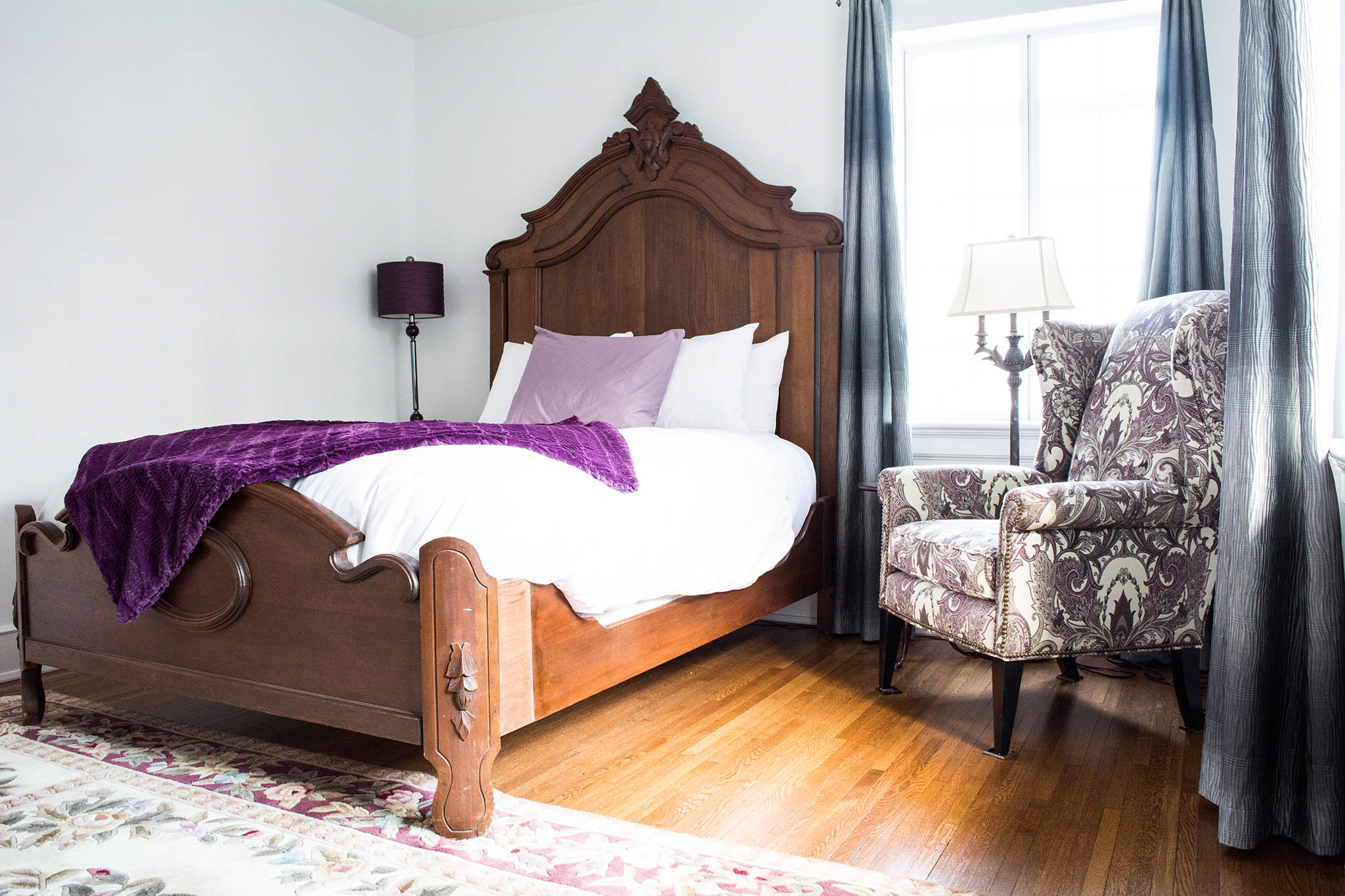 Wilson Suite bedroom. Large bed with white comforter and purple throw blanket. Hardwood floors and a chair in the corner of the room.