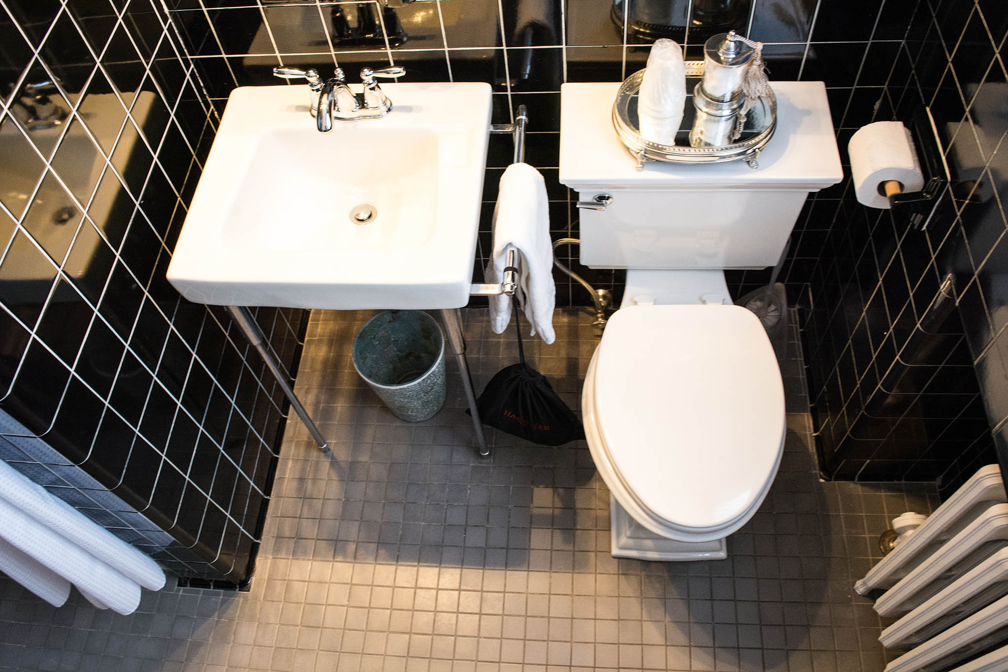Wilson Suite bathroom. A white sink and toilet, surrounded by black wall tile.